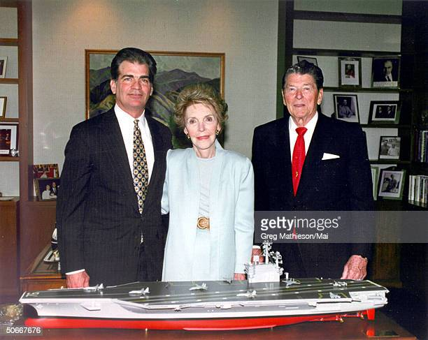 Newport News President and CEO William P Fricks standing w Nancy Reagan and President Reagan behind scale model of US Navy's multipurpose nuclear...
