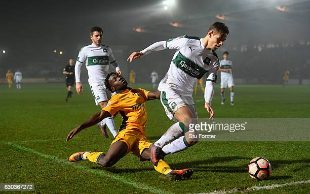 Newport player Jordan Green is warded off the ball by Oscar Threlkeld of Plymouth during The Emirates FA Cup Second Round Replay between Newport...
