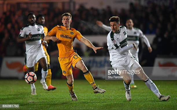 Newport player Rhys Healey challenges Sonny Bradley of Plymouth during The Emirates FA Cup Second Round Replay between Newport County and Plymouth...