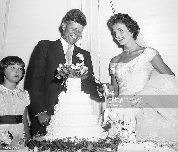 Democratic Senator John F Kennedy and his bride the former Jacqueline Lee Bouvier cut their wedding cake after their marriage yesterday at St Mary's...