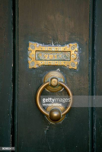 a close view of an old door knocker and mail slot. - door knocker stock photos and pictures