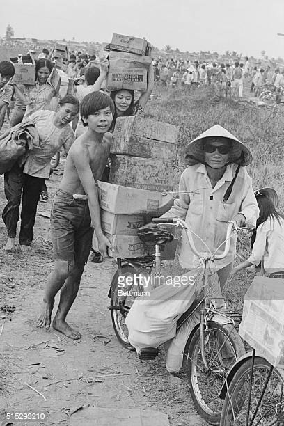 Newport South Vietnam South Vietnamese civilians carry as much as they can after plundering the US commissary at Newport just outside Saigon The...