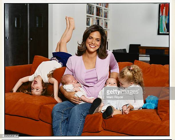 News anchor Soledad O'Brien holds her twin sons Charlie and Jackson on the sofa with her daughters Sofia and Cecilia