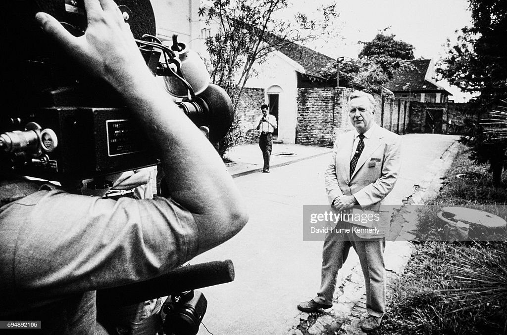 CBS news anchor Walter Cronkite (right, in suit) reports from outside of the 'Plantation' POW camp, March 30, 1973, in Hanoi, Vietnam. Cronkite was in the country to cover the last of the US POW release.