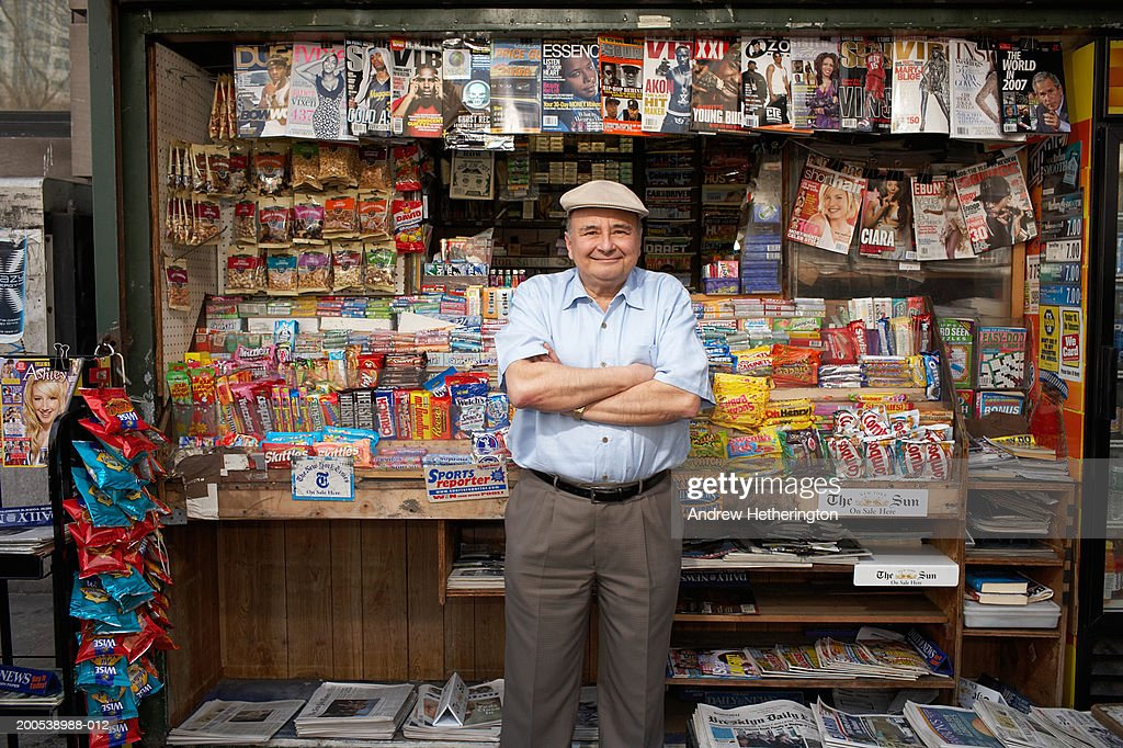 News and magazine kiosk operator in front of stand, portrait : Stock Photo