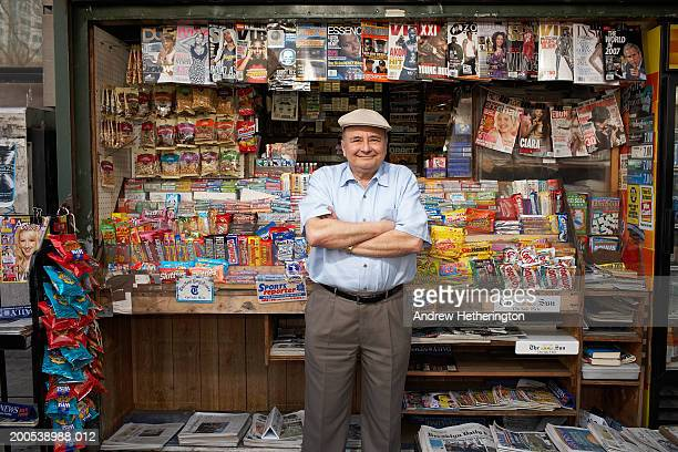 News and magazine kiosk operator in front of stand, portrait