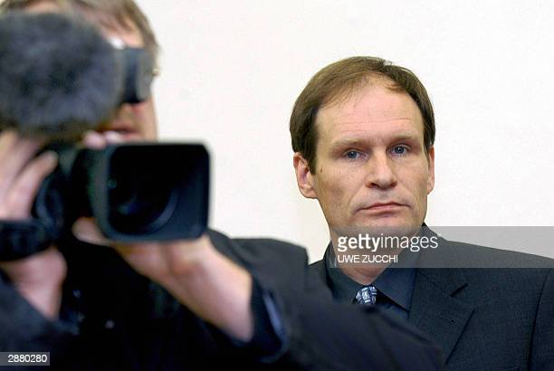 A news cameraman films as German selfconfessed cannibal Armin Meiwes waits for the start of his trial for having killed and eaten a man BerndJuergen...