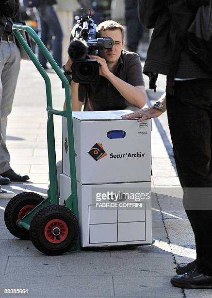 A news cameraman films documents on June 10 2009 on the opening day of Cecile Brossard's trial at the courthouse in Geneva Banker Edouard Stern one...