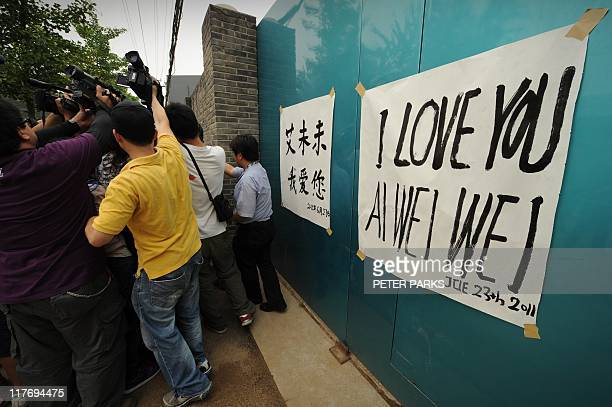News cameramen chase supporters of outspoken Chinese artist Ai Weiwei after they put up banners saying i love you Ai Weiwei in English and Chinese at...