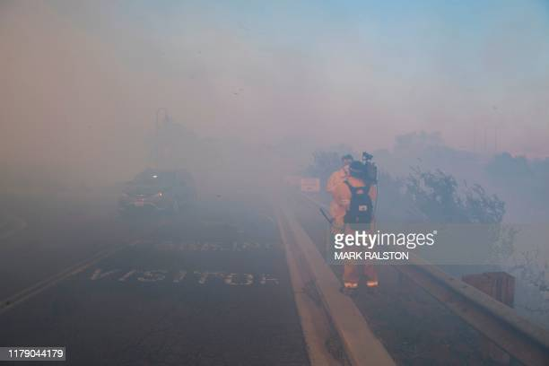 A news crew reports from the driveway of the Reagan Library as firefighters battle to protect it from the Easy Fire in Simi Valley California on...