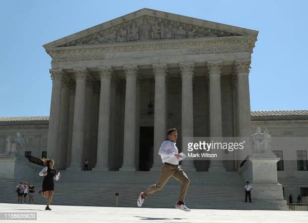 News intern Brannon Dewolf runs with a decision released by theU.S. Supreme Court, on June 27, 2019 in Washington, DC. The high court blocked a...