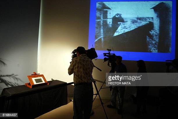 "News media cameramen photograph a pewter plate of the first known photograph ""Poin de Vue du Gras"" by Nicephore Niepce made in 1826 on display at the..."
