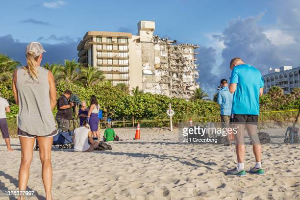 News media crew reporting and local residents on the beach looking at the collapsed Champlain Towers condimium, Surfside, Miami Beach, Florida.