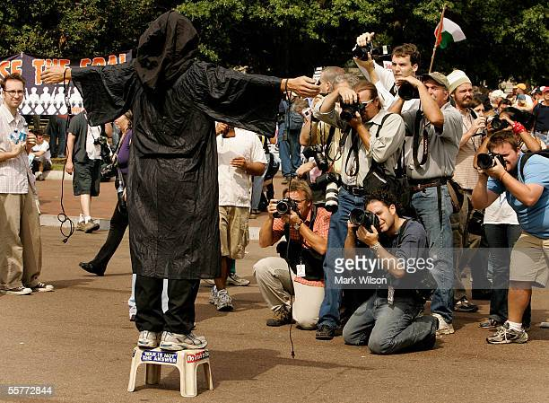 News media gather around an AntiWar protester wearing Abu Ghraib prison garb during a protest in front of the White House September 26 2005 in...