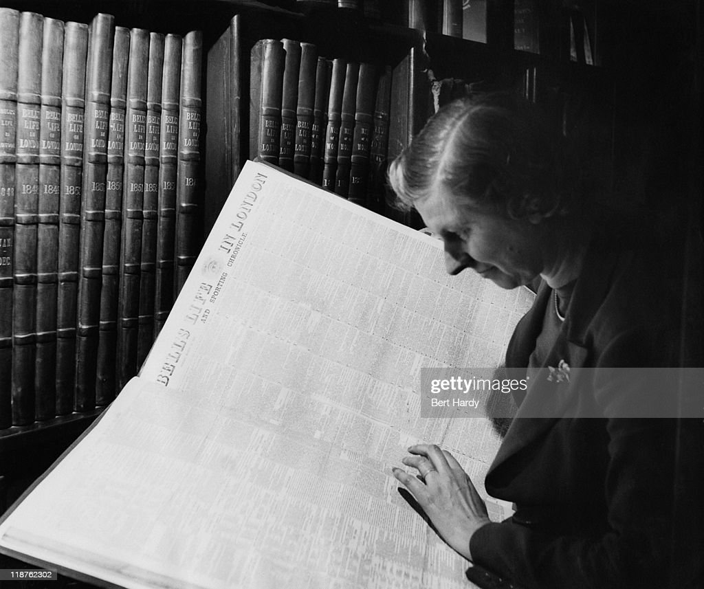 News of The World columnist 'Julia King' at work in the newspaper's library, April 1953. She is consulting a bound volume of copies of Bell's Life In London, the precursor of News Of The World. Original Publication : Picture Post - 6488 - The News of The World - pub. 18th April 1953.
