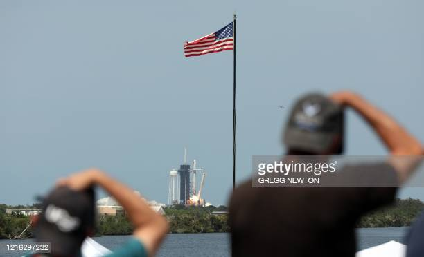 News photographers record the historic first manned launch of the SpaceX Falcon 9 rocket carrying the Crew Dragon spacecraft as it lifts off from...