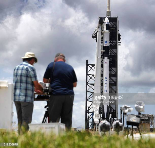 News photographers set up remote cameras as the Crew Dragon capsule sits on top of the SpaceX Falcon 9 rocket at Launch Complex 39A at Kennedy Space...