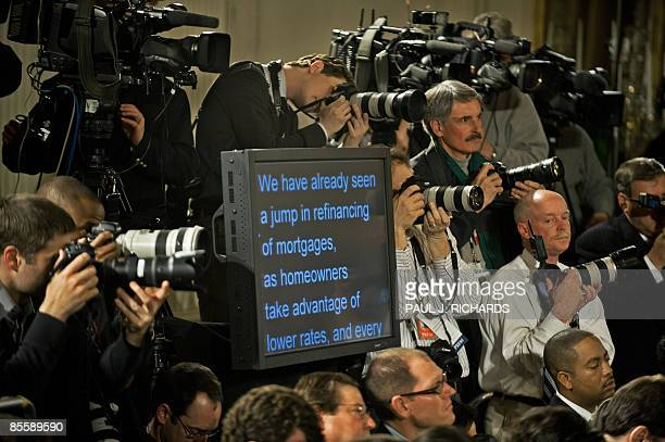 News photographers surround the teleprompter as US President Barack Obama delivers opening remarks during his prime-time press conference in the East...