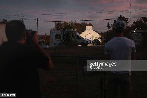 News photographers take pictures as the sun begins to rise on First Baptist Church of Sutherland Springs on November 6 2017 in Sutherland Springs...