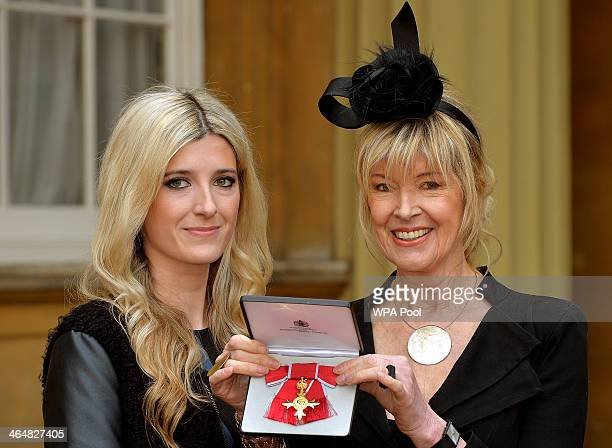 News presenter Julia Somerville, stands with her daughter Rachael , as she holds her OBE presented to her by the Prince of Wales at Buckingham Palace...