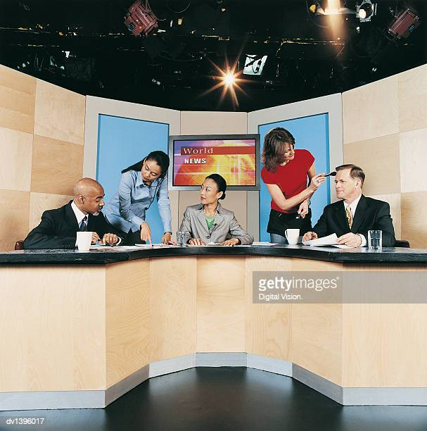 TV News Presenters, Make-up Artist and a Producer in a TV Studio