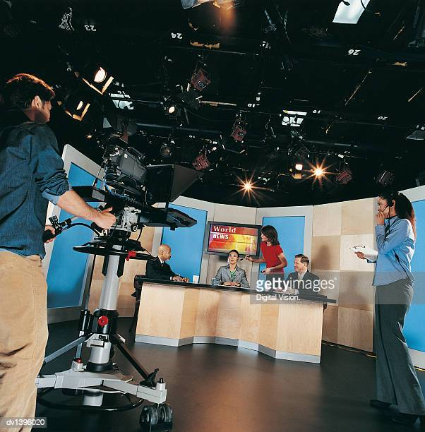 TV News Presenters, Make-up Artist, Cameraman and a Producer in a TV Studio