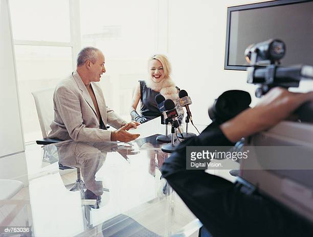 News Reporter Interviewing a Female Pop Musician Sitting at a Table With a TV Cameraman