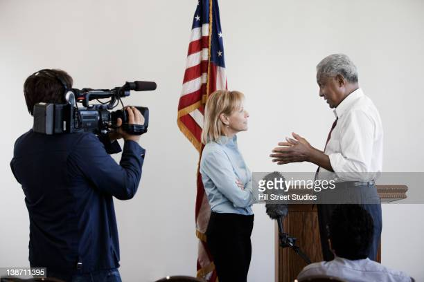 news reporter interviewing politician on camera - cinematographer stock pictures, royalty-free photos & images