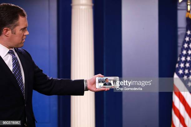 News reporter Peter Alexander watches the arrival of French President Emmanuel Macron on an iPhone while waiting for the White House press briefing...