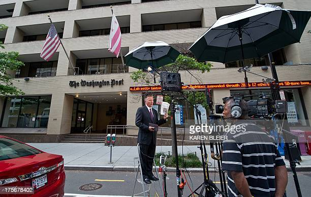 NBC News reporter Tom Costello does a standup holding the August 6 2013 edition in front of the Washington Post August 6 2013 in Washington DC the...