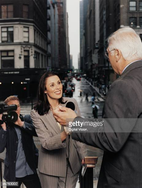 News Reporter With a Tv Cameraman interviewing a Mature Man in a Suit