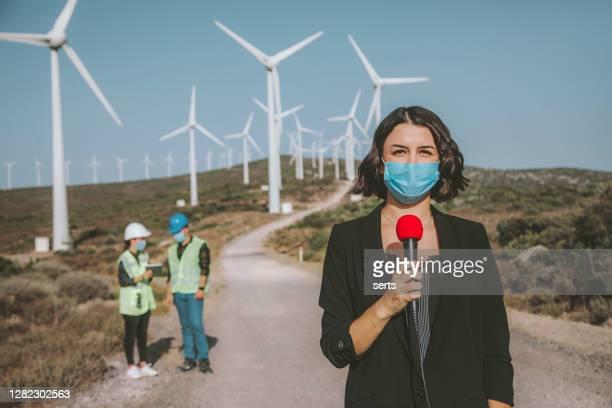 tv-nyheter reporter kvinna med ansiktsmask gör reportage om en förnybar energi under pandemi - journalist bildbanksfoton och bilder