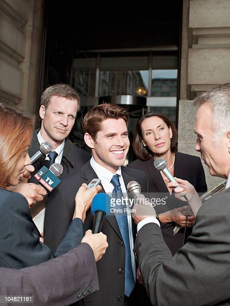 News reporters interviewing smiling man outside courthouse