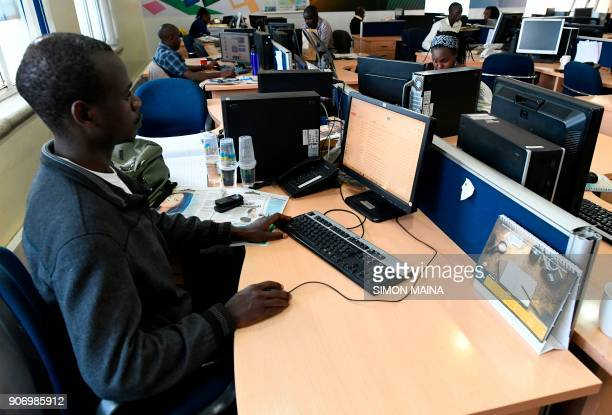 NTV news reporters work from their desks in a newsroom of Kenyan 'Nation Media Group' in Nairobi on January 19 2018 / AFP PHOTO / SIMON MAINA