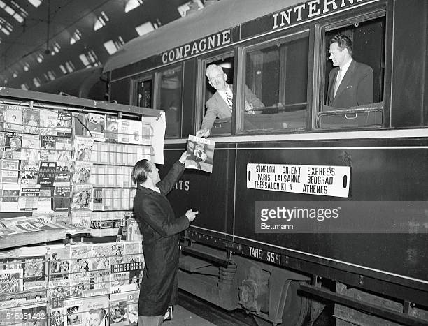 A news stand vendor hands a magazine to a passenger before departure of the SimplonOrient Express