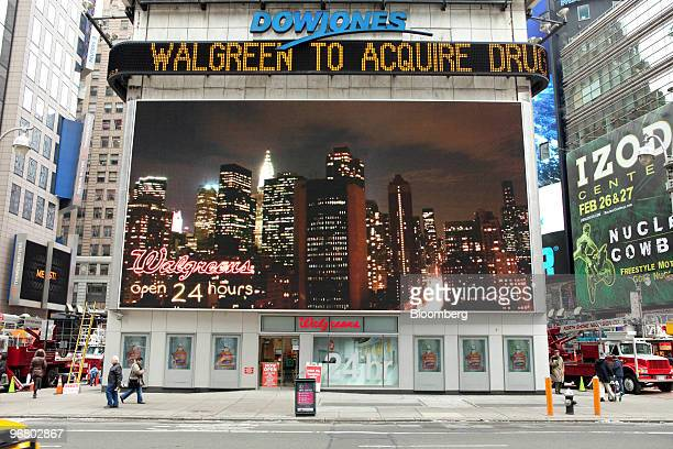 A news ticker displays a headline about Walgreen acquiring Duane Reade outside a Walgreen's store in New York US on Wednesday Feb 17 2010 Walgreen Co...
