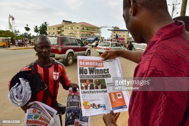 A news vendor sells a copy of The Democrat newspaper in a street of Monrovia on October 13 2017 following the announcement of the partial results of...