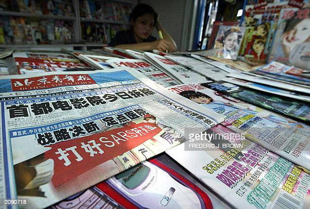 A news vendor sits in her shaded stall behind a selection of publications for sale 17 June 2003 in Beijing After gagging the staterun press for...