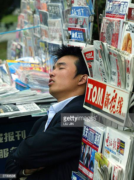 A news vendor takes a nap at his stall along a street in Shanghai 16 November 2003 China may be succeeding in its attempt to cool its overheating...
