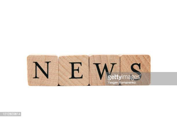 news word made of wooden cubes, isolated on white background - salle de presse photos et images de collection