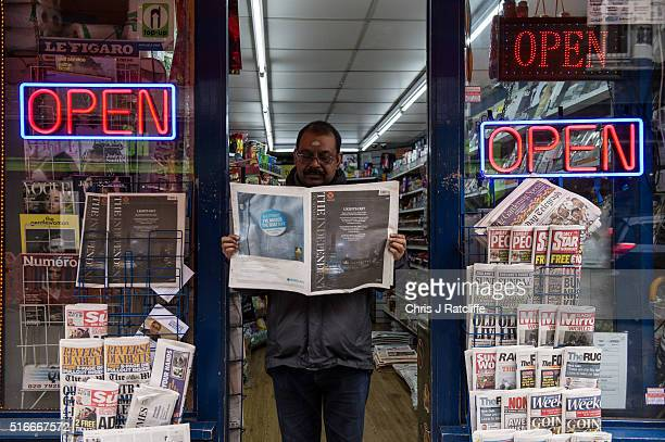 A newsagent reads the last ever print edition of The Independent On Sunday outside his shop in Soho on March 20 2016 in London England The newspaper...