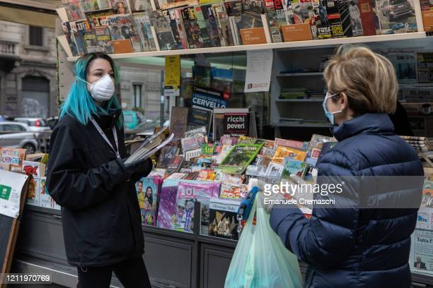 A newsagent speaks to an elderly woman in front of her news kiosk on March 11 2020 in Milan Italy The Italian Government has strengthened up its...