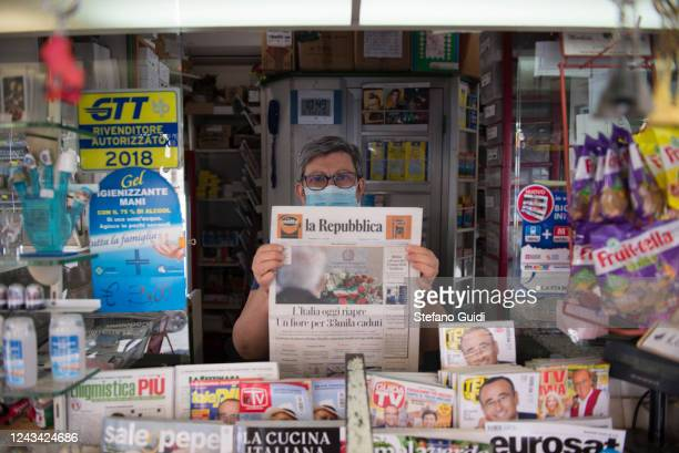 A newsagent wearing a protective mask holds the Italian newspaper La Repubblica with the headline Italy reopens today a flower for 33 fallen miles on...