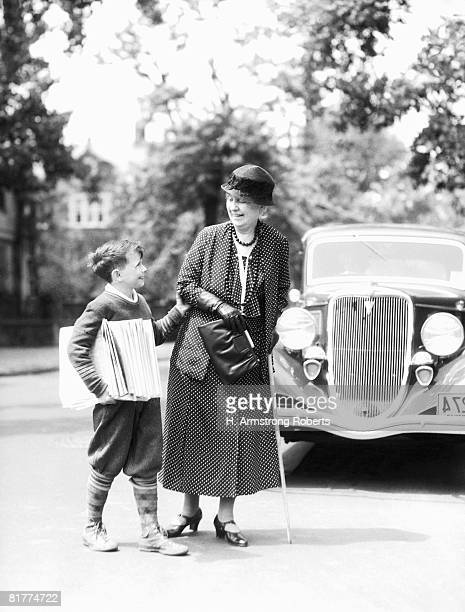 newsboy with stack of papers under arms, helping elderly woman with cane cross street. - deed stock photos and pictures