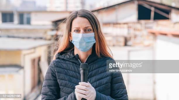 newscaster präsentiert die brisante nachricht während der covid-19-pandemie - journalist stock-fotos und bilder