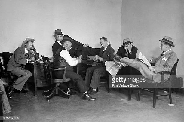 Newsmen sit around the newsroom playing cards reading the paper and talking on the phone