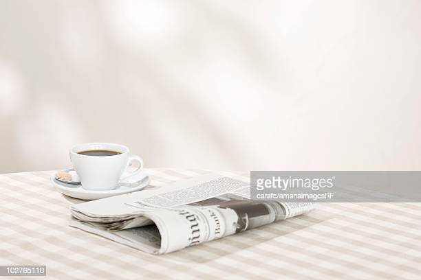 A newspaper and a cup of coffee on a table