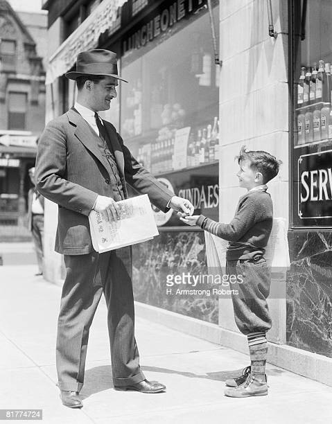 Newspaper boy selling paper to businessman, Philadelphia.