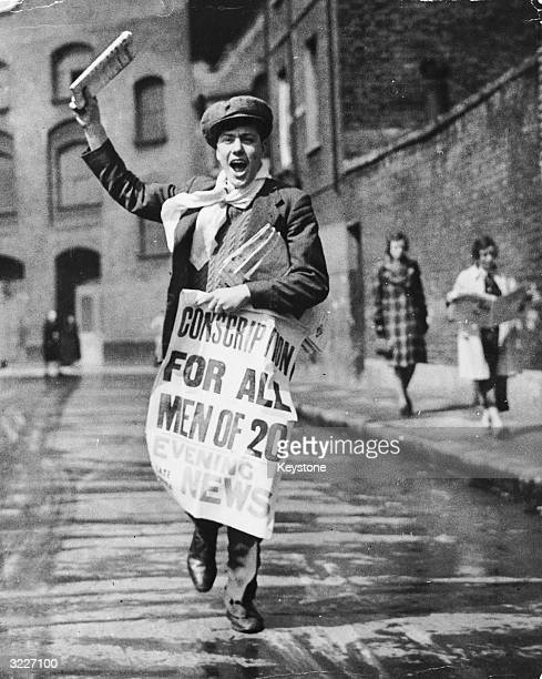 A newspaper boy with a poster calling for the conscription of all 20yearold men during World War II
