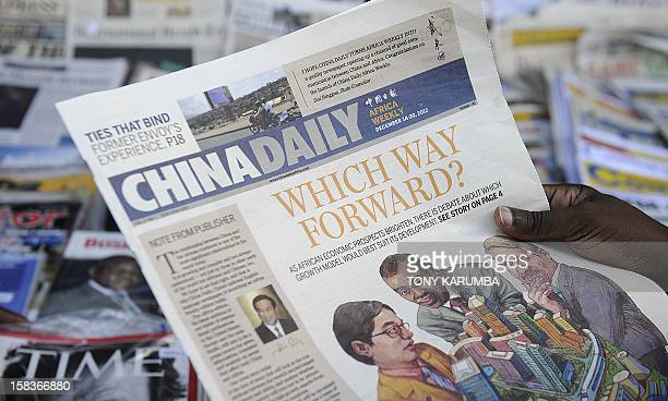 Newspaper consumer reads a copy of China's Africa edition of its daily newspaper infront of a news stand in the Kenyan capital on December 14, 2012....
